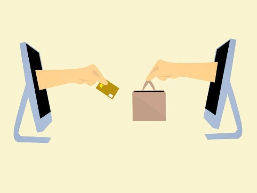 Grafik mit zwei Händen, die aus zwei Computern kommen. Eine hat eine Kreditkarte in der Hand, eine eine Shoppingtüte.