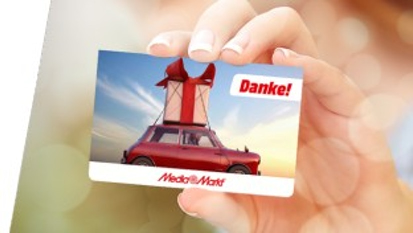 Eine Frauenhand hält eine Geschenkkarte von MediaMarkt