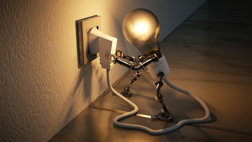 Glühbirne mit Armen und Beinen steckt eigenes Netzkabel in die Steckdose