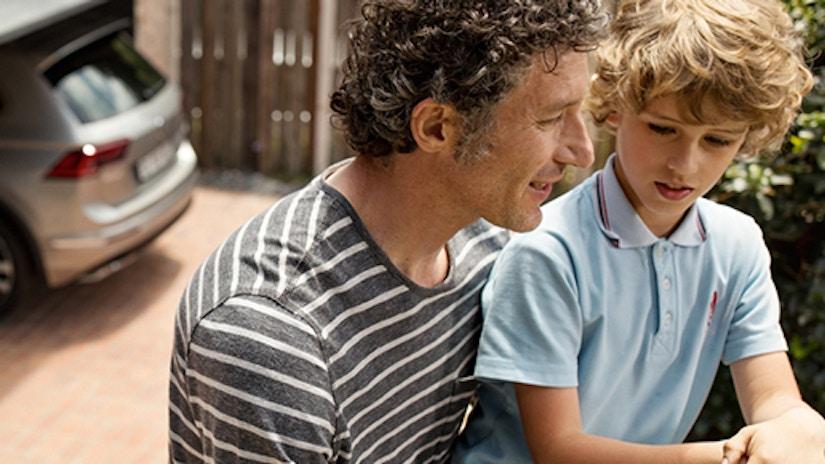Ein Vater und sein Sohn sitzen vor einem Auto