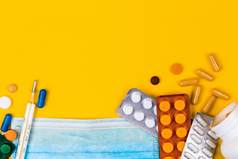 Fieberthermometer, Mundschutz und verschiedene Tabletten auf gelber Oberfläche