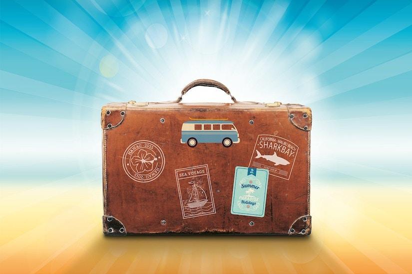 Brauner Koffer mit verschiedenen Aufklebern drauf