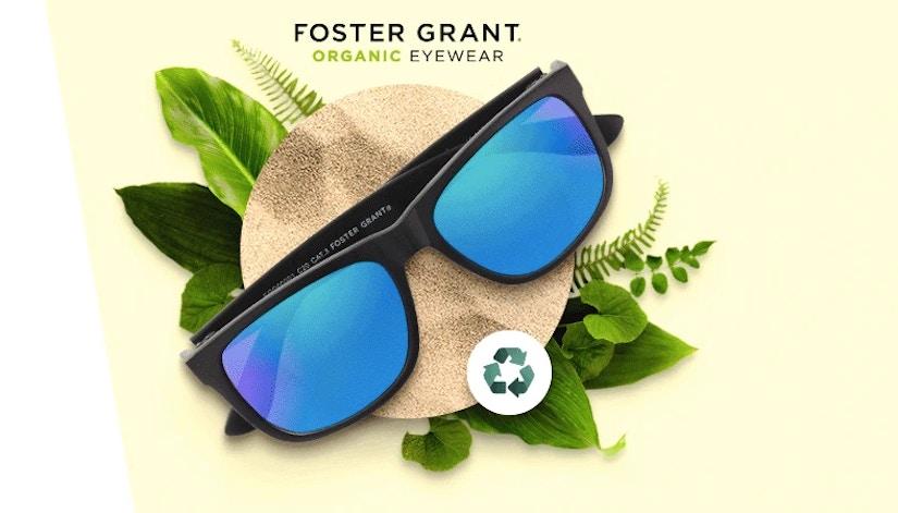 Reflexierende Sonnenbrille mit Umwelt-Logo auf grünen Blättern.