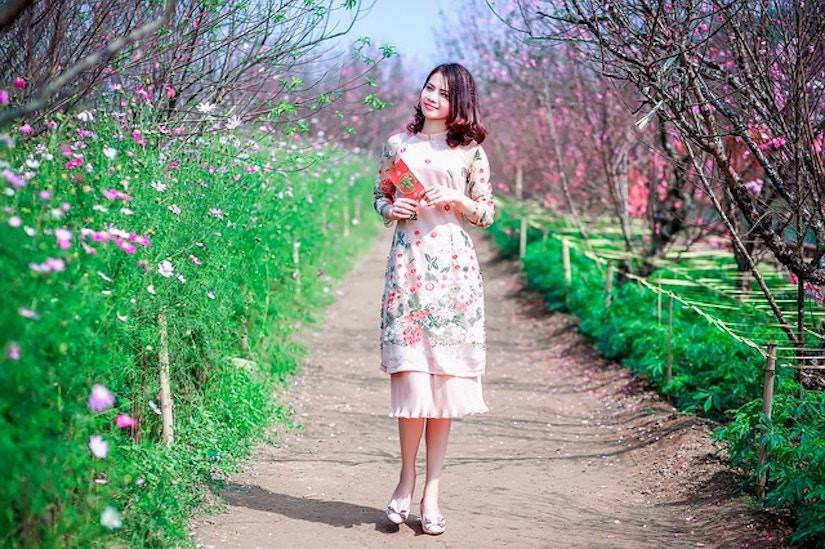 Frau mit Blumenkleid zwischen Pflanzenreihen.