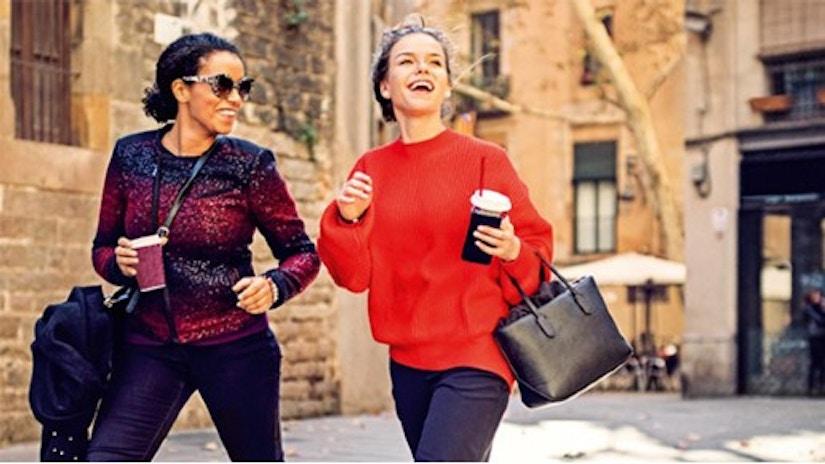 Zwei Freundinnen sind shoppen und lachen dabei.