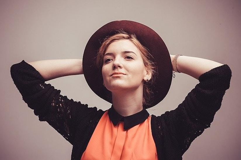 Frau mit orange-schwarzem Top und Hut.