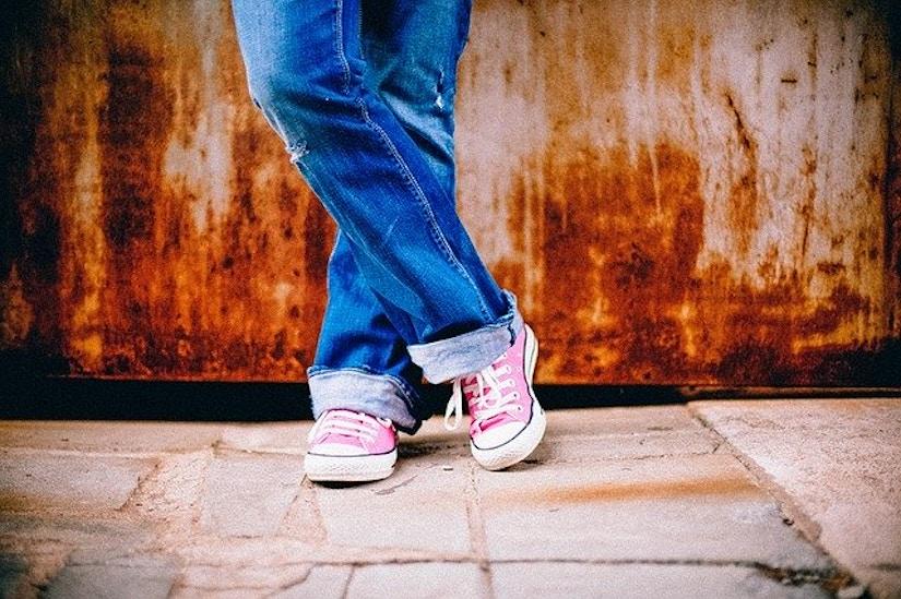 Beine mit Jeans und Turnschuhen