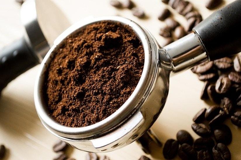 Siebträger mit Kaffeemehl neben Kaffeebohnen