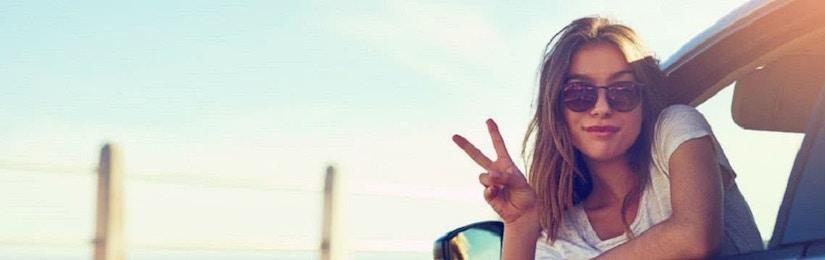 Frau lehnt sich lässig aus dem Autofenster und macht ein Peace-Zeichen