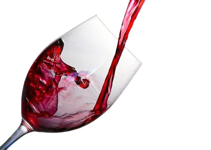 Rotwein wird in Weinglas eingegossen