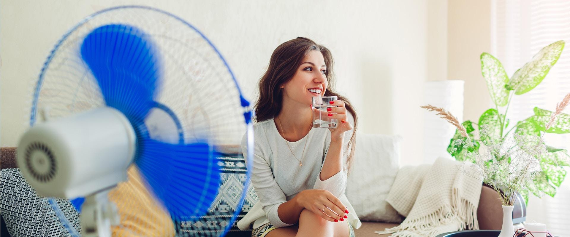 Eine Frau sitzt vor einem Ventilator und trinkt ein Glas Wasser.