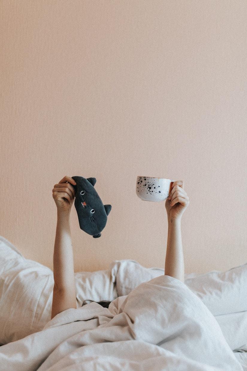 Person im Bett hält Kaffeetasse in die Höhe