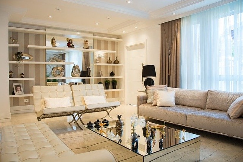 Helles Wohnzimmer mit Design-Couch und Sitzecken um verspiegelten Tisch.