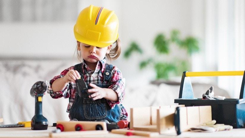 Ein kleines Mädchen mit einem Helm baut an einer Werkbank.