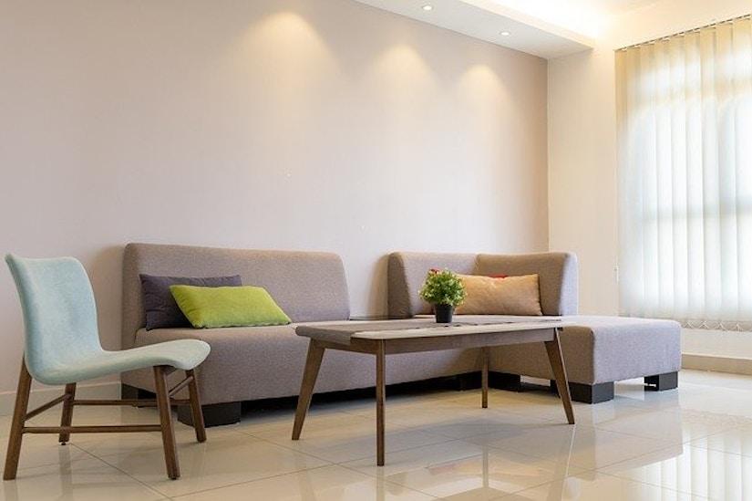 Modernes Sofa mit Design-Stuhl und moderenem Couchtisch aus Holz.