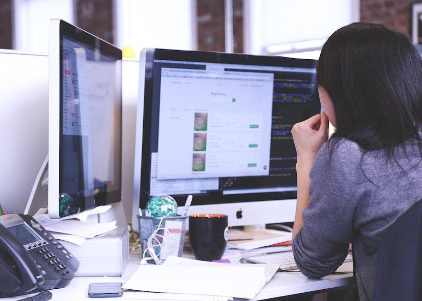 Eine Frau sitzt am Arbeitstisch und guckt in den Bildschirm