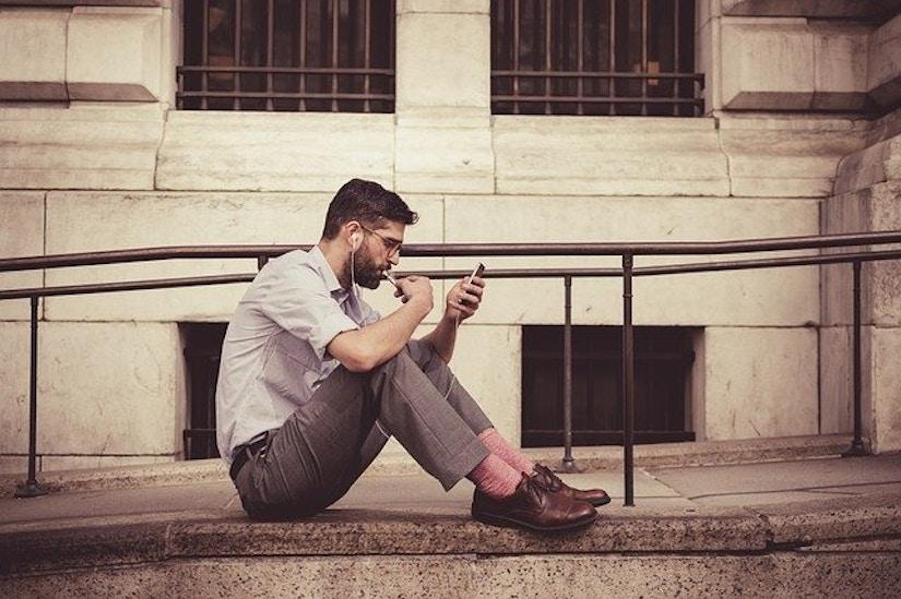 Mann telefoniert vor altem Gebäude