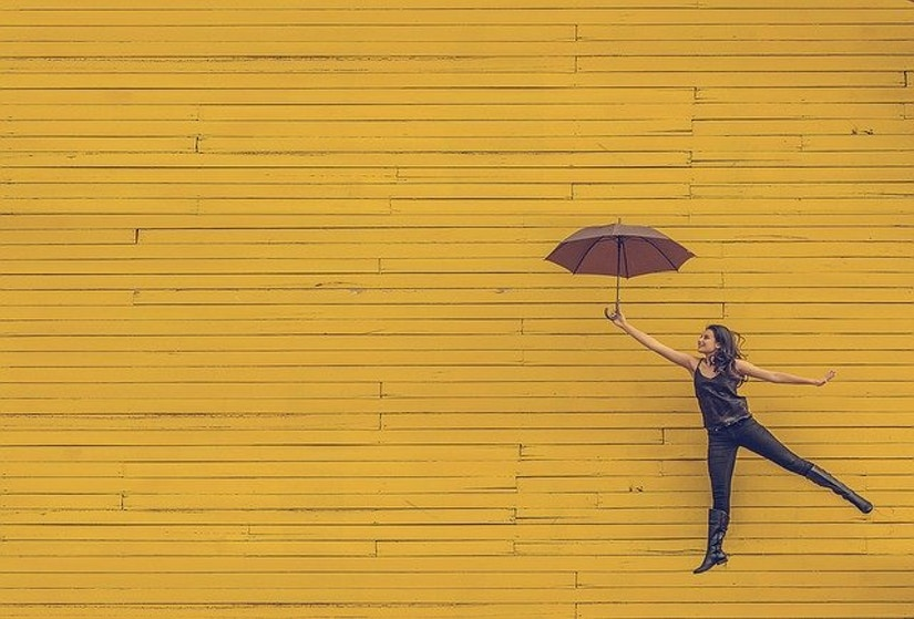 Frau mit Regenschirm vor gelber Wand