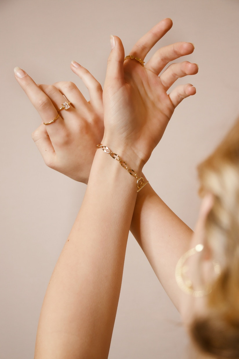 Goldarmband und Ringe an Frauenarm