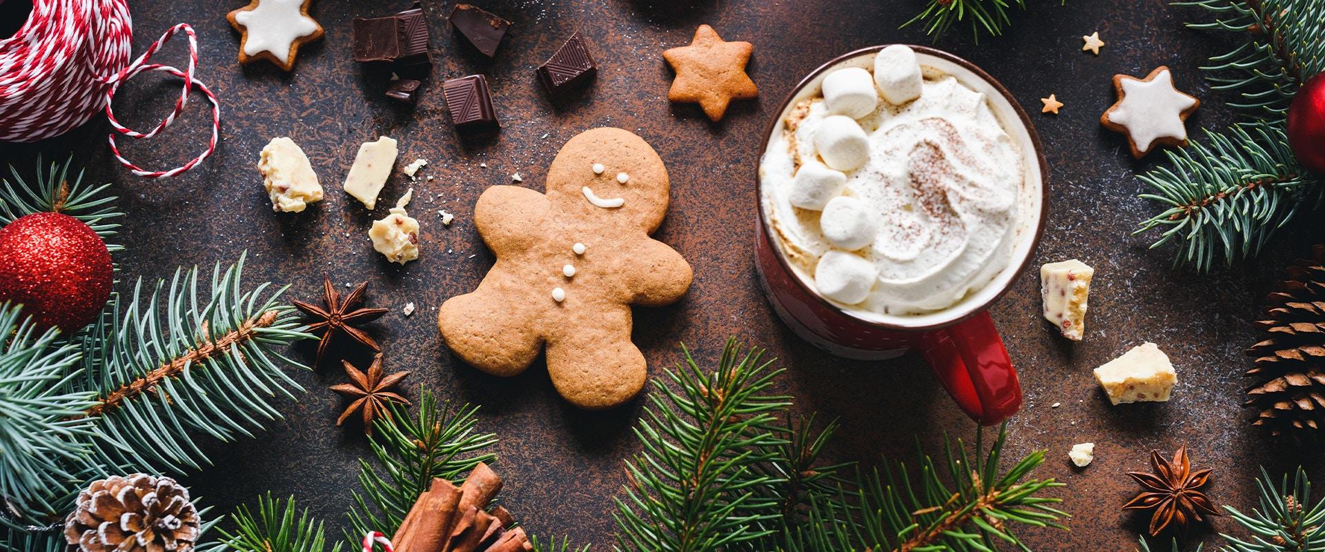 Ein Lebkuchenmann liegt auf einem Tisch. Neben ihm steht eine Tasse mit heißer Schokolade. Um ihn herum liegt Weihnachtsschmuck.