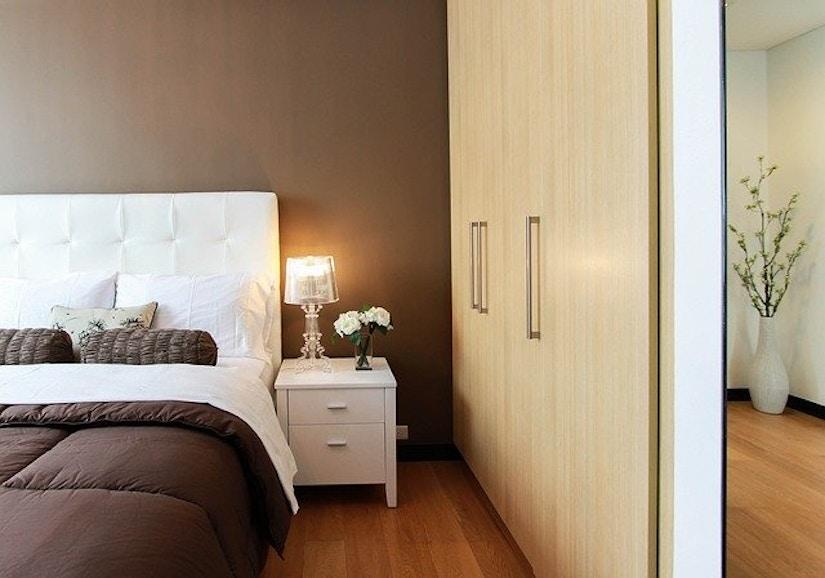 Schlafzimmer mit Bett, Nachttisch, Schrankwand und Spiegel.