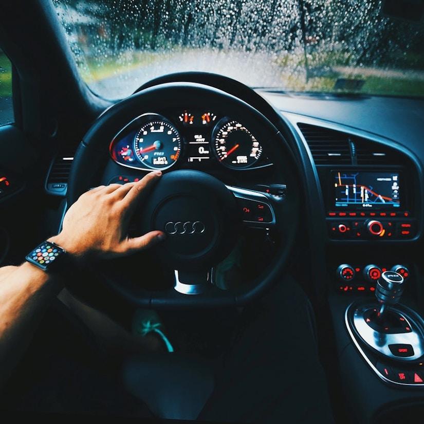 Ein Mann sitzt am Steuer eins Audi