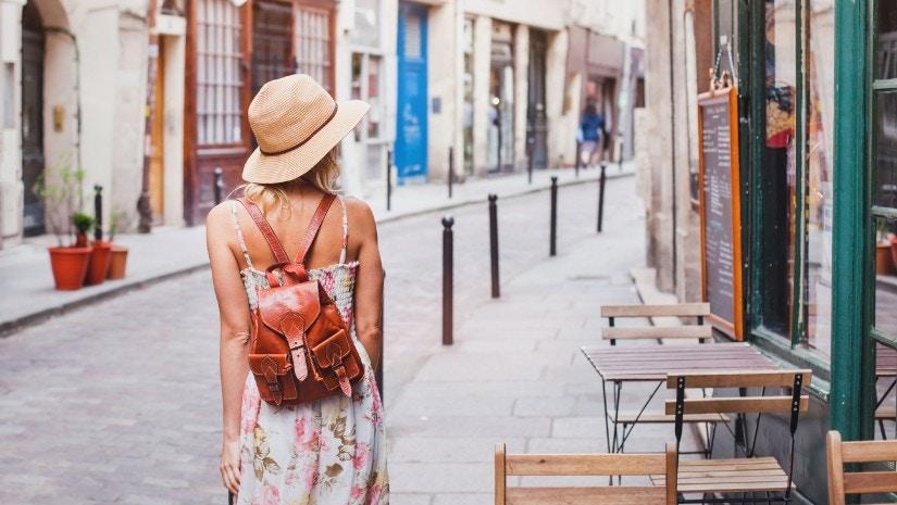 Eine Frau schlendert durch eine Altstadt.