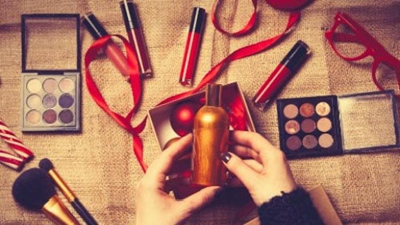 Eine Frauenhand packt Kosmetikgeschenke ein.