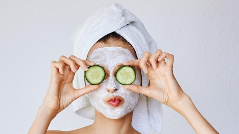 Eine Frau mit Gesichtsmaske und Gurken auf den Augen
