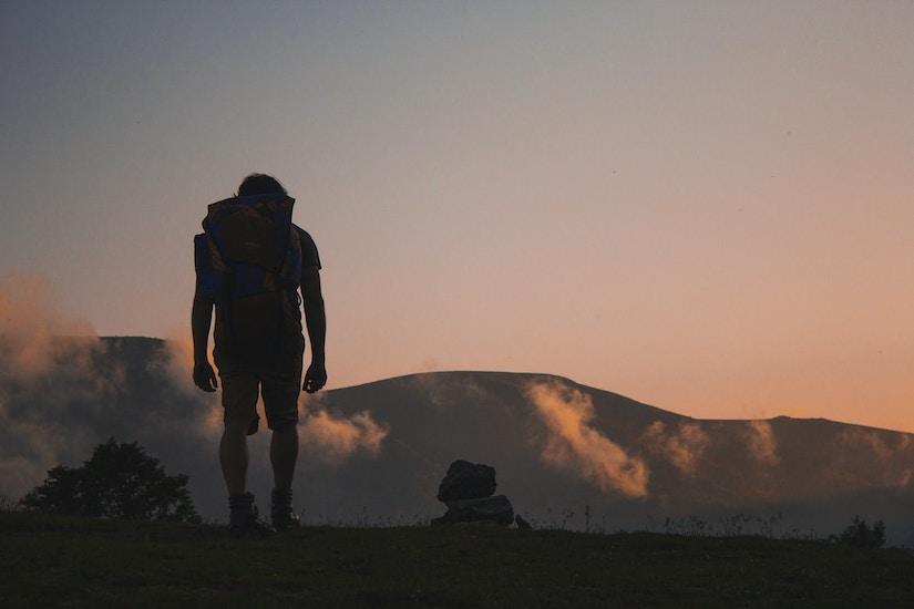 Ein Reisender mit dem großen Rucksack beobachtet den Sonnenuntergang