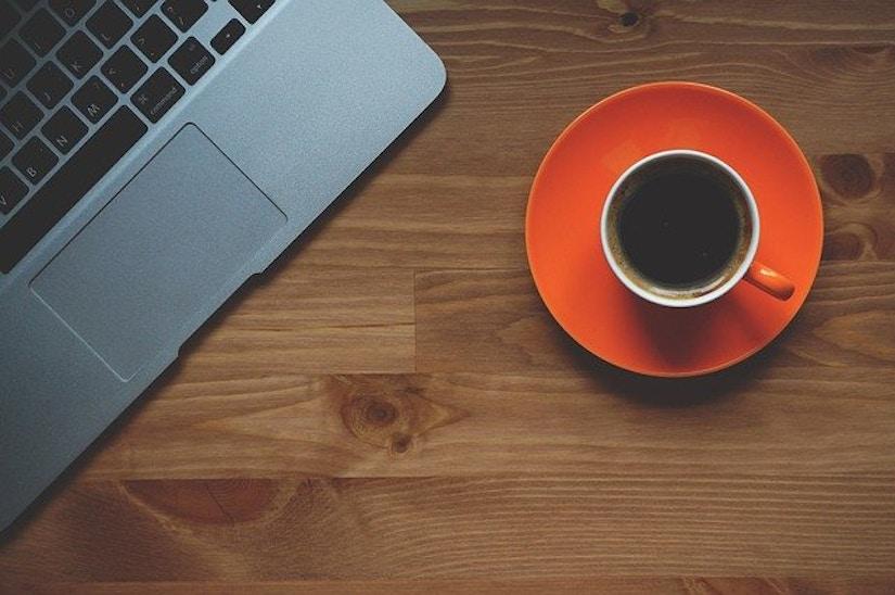 ausschnitt eines Laptops mit Kaffeetasse