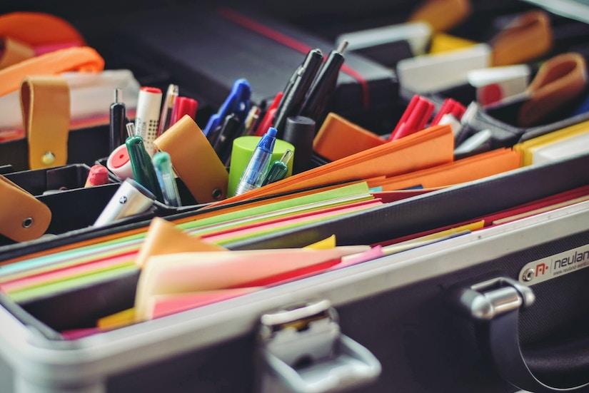 Buntes Papier, Stifte und weitere Schreibwaren in Koffer