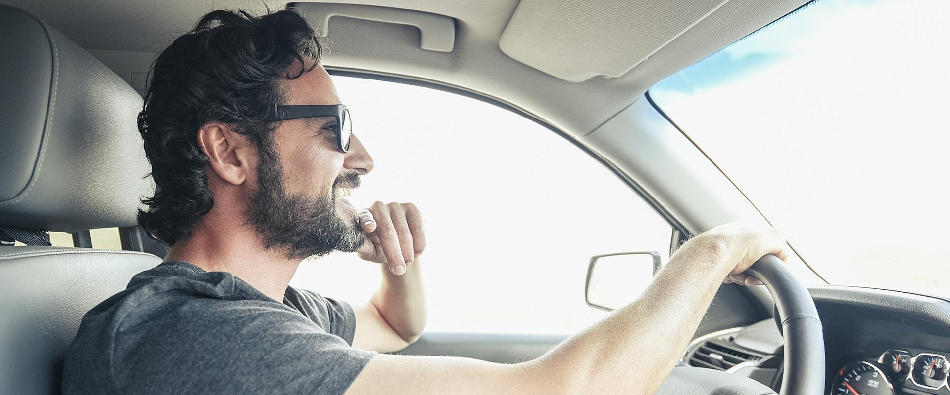 Ein Mann fährt Auto.