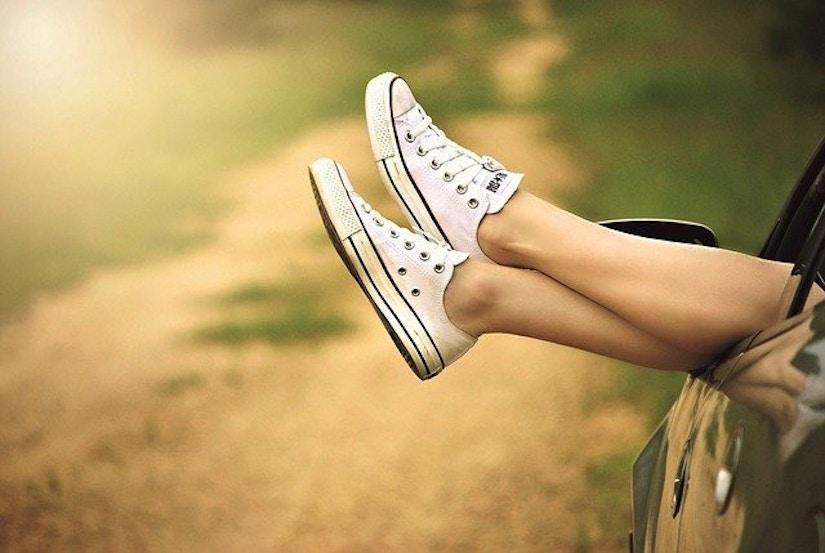 Beine, die aus dem Autofenster baumeln mit weißen Sneakern