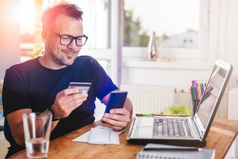Ein Mann sitzt mit Kreditkarte und Smartphone vor seinem Laptop und lächelt