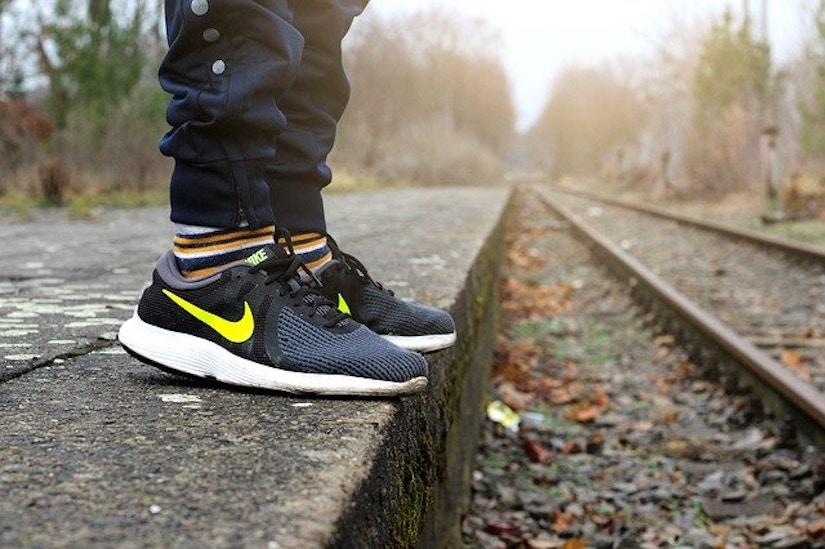 Nahaufnahme auf Nike Sneaker an herbstlicher Bahnstrecke