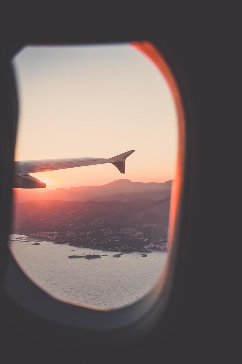 Blick aus dem Fenster einer Passagiermaschine im Sonnenuntergang