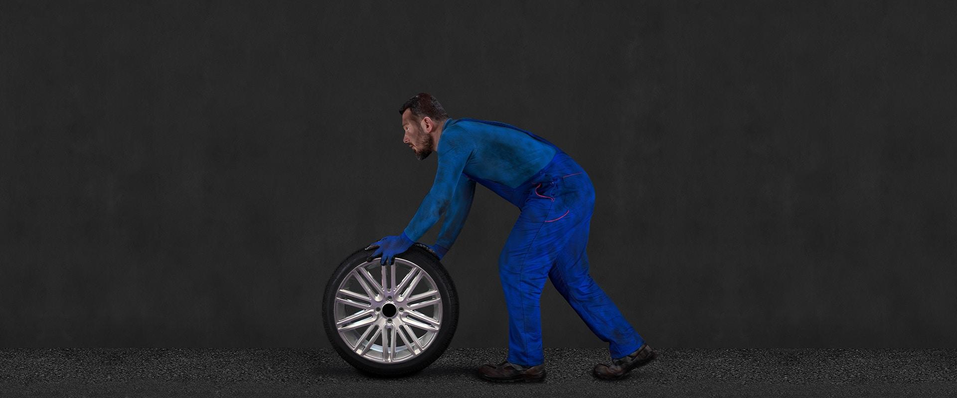 Ein Mann in einem blauen Overall rollt einen Reifen