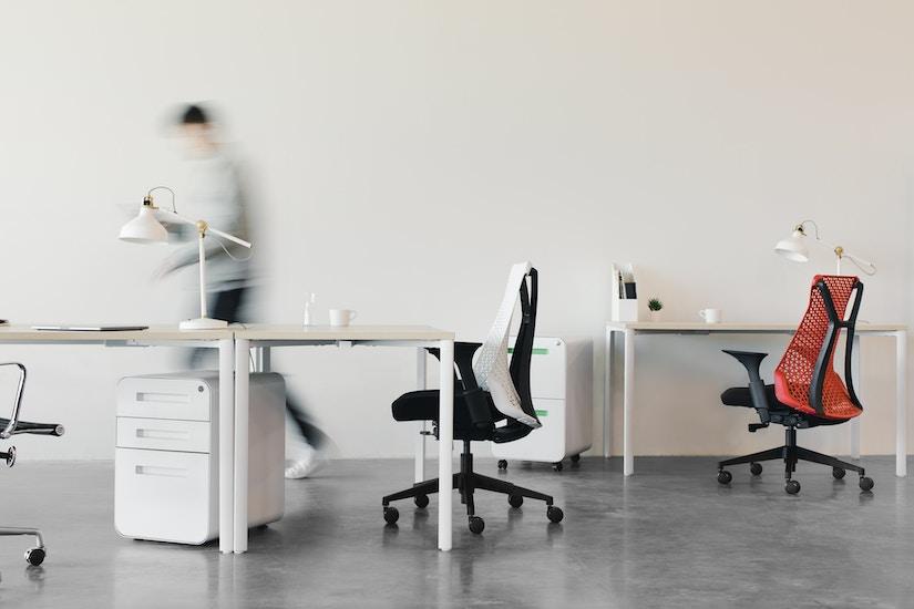 Hell eingerichtetes Büro mit Tischen und Bürostühlen