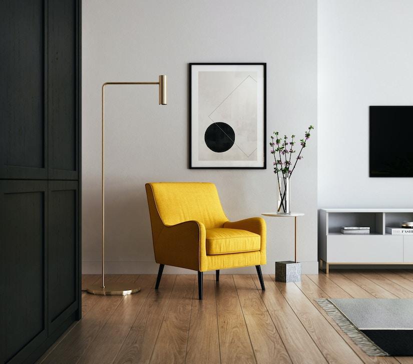 Schick eingerichteter Raum mit Parkett, Designlampe und gelbem Sessel