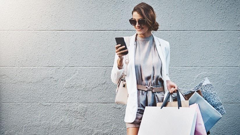 Eine Frau hat Einkaufstüten in der Hand und schaut lächelnd auf ihr Handy.