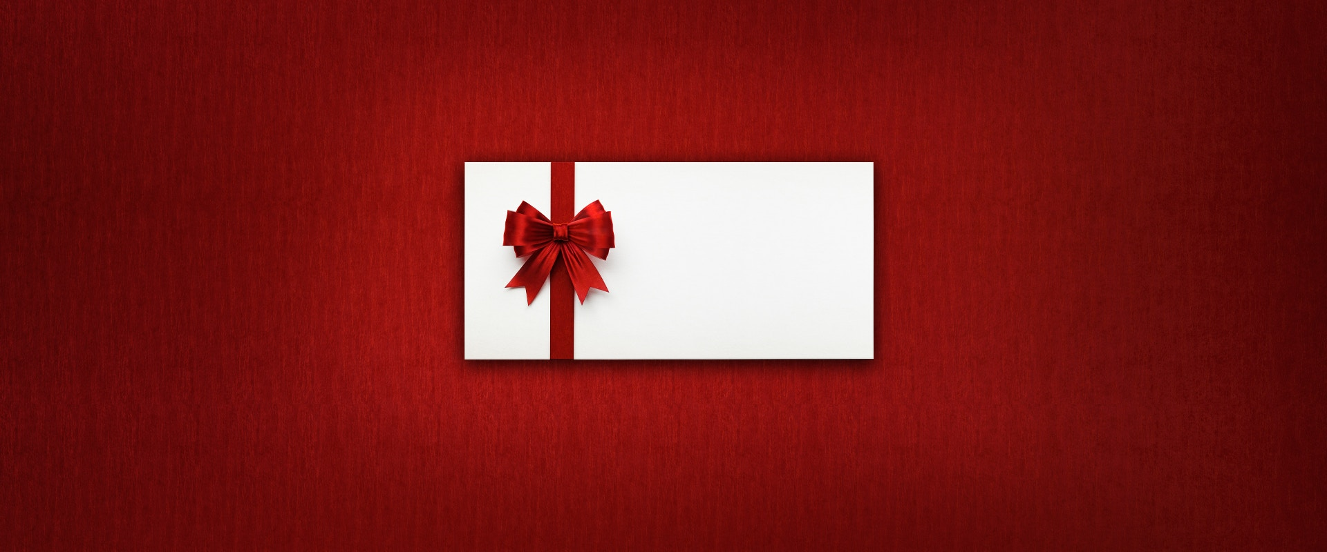 Ein Geschenkgutschein mit Schleife auf rotem Hintergrund.