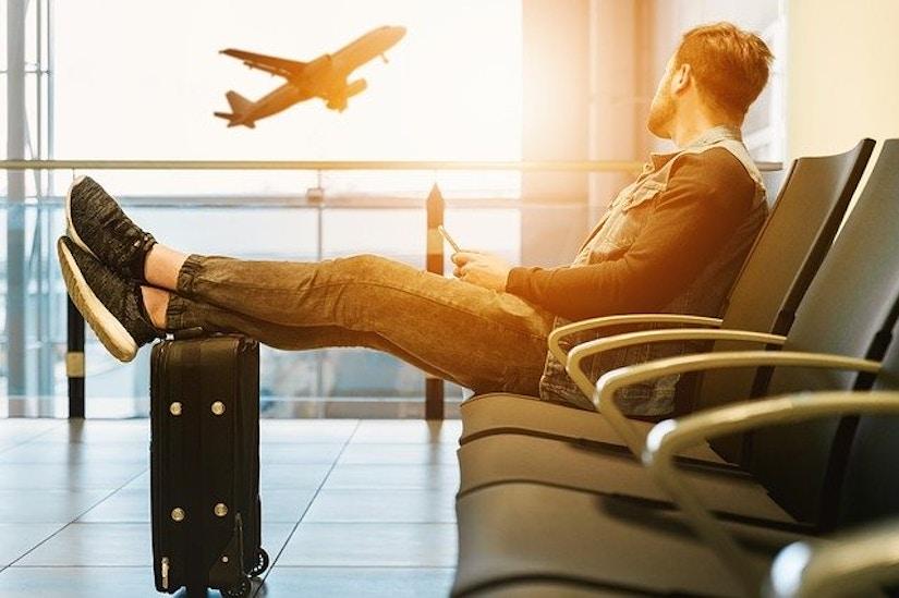 Mann sitzt auf Flughafen-Bank. Im Hintergrund startet ein Passagierflugzeug.