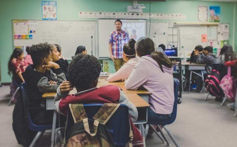 Lehrer steht in Klassenraum umgeben von sitzenden Kindern