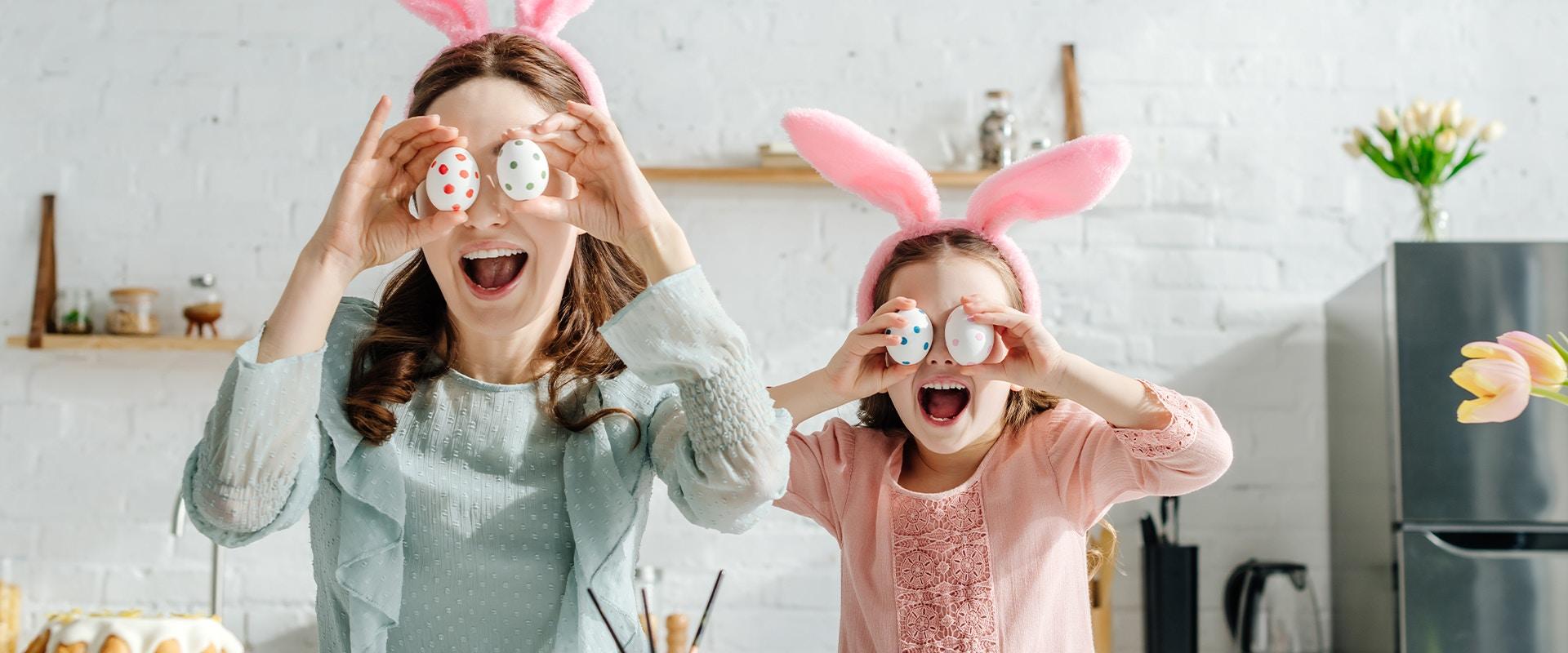 Eine Mutter und ihre Tochter tragen Hasenohren auf dem Kopf und halten sich bemalte Eier vor die Augen.
