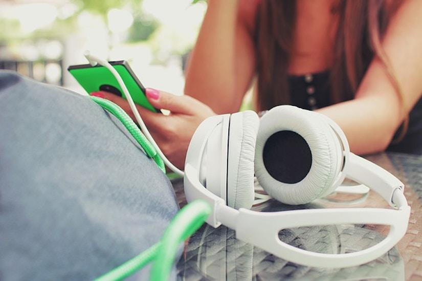 Frau mit Smartphone und weißem Kopfhörer an Cafétisch