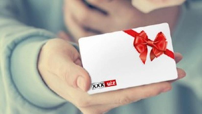 Eine Männerhand, die einen XXXLutz Geschenkgutschein hält