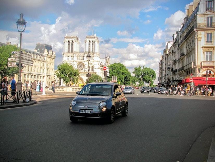 Fiat auf pariser Straße. Im Hintergrund die Kathedrale Notre Dame.