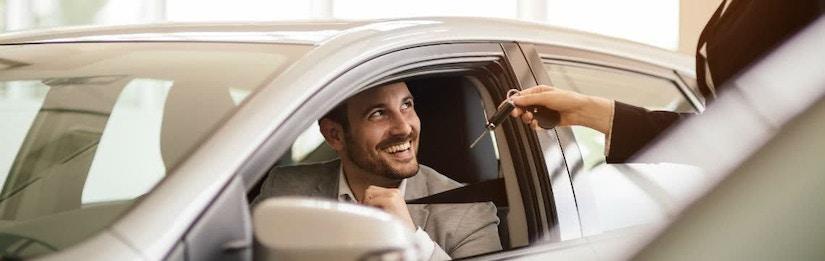 Mann sitzt auf der Fahrerseite und nimmt lächelnd den Autoschlüssel entgegen
