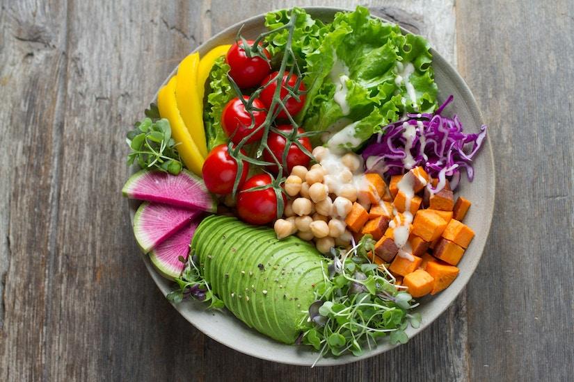 Teller mit Blattsalat, Avocado, Paprika und weiteren veganen Lebensmitteln